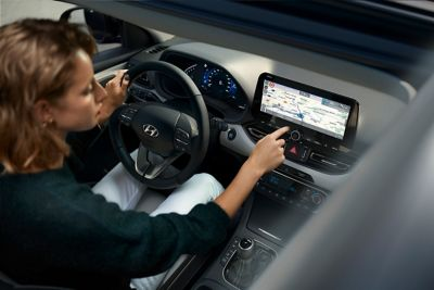 Woman behind the wheel of her Hyundai i30 Wagon, using her navigation touchscreen