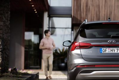 The new Hyundai Santa Fe Hybrid pictured parked in front of a stylish house.