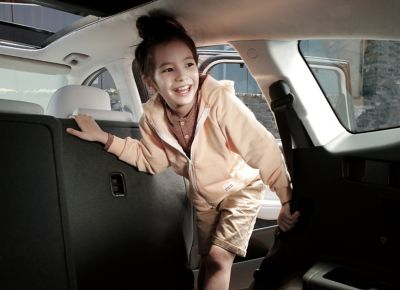 A little girl getting in the backseat of the new Hyundai Santa Fe Hybrid 7 seat SUV.