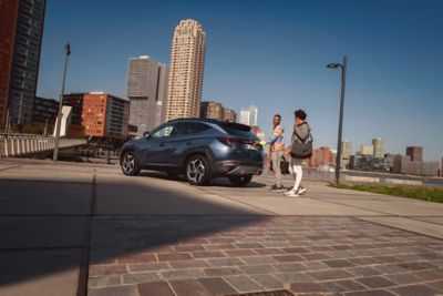 The all-new Hyundai Tucson Hybrid compact SUV parked on a city street pictured from the side.
